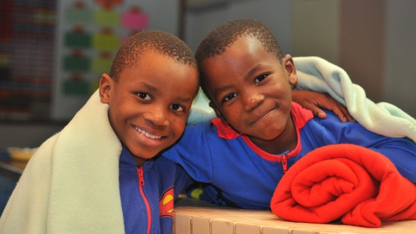 Orphans in the South African ACVV Khayalethu Youth Centre are happy to receive warm blankets provided by Schaeffler.